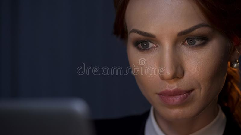Beautiful business lady working on laptop, looking on screen at night office stock photos