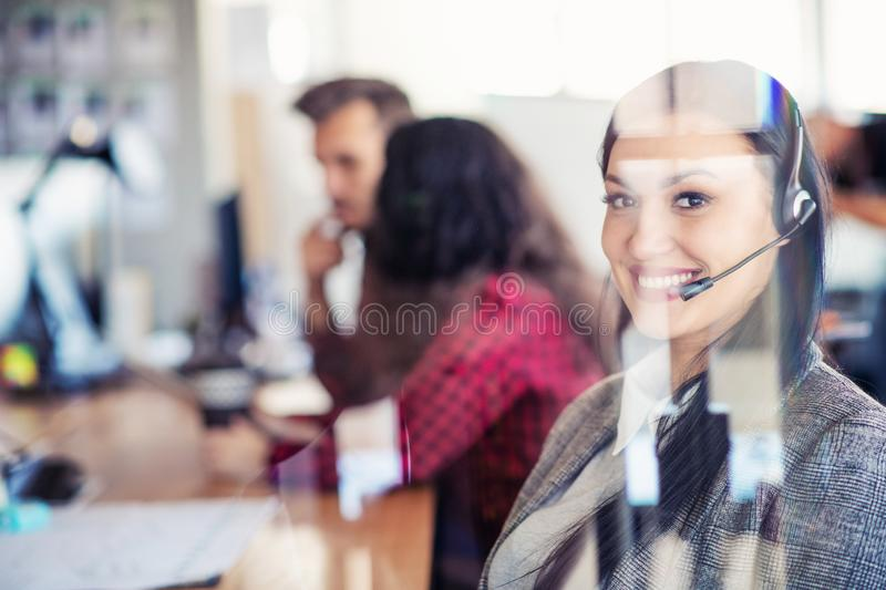 Beautiful business people in headsets are using computers and smiling while working in office. Girl is looking at camera royalty free stock image