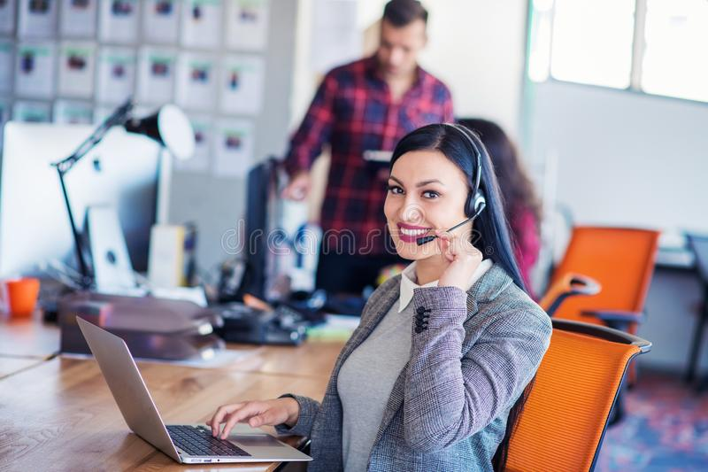 Beautiful business people in headsets are using computers and smiling while working in office. Girl is looking at camera stock photos