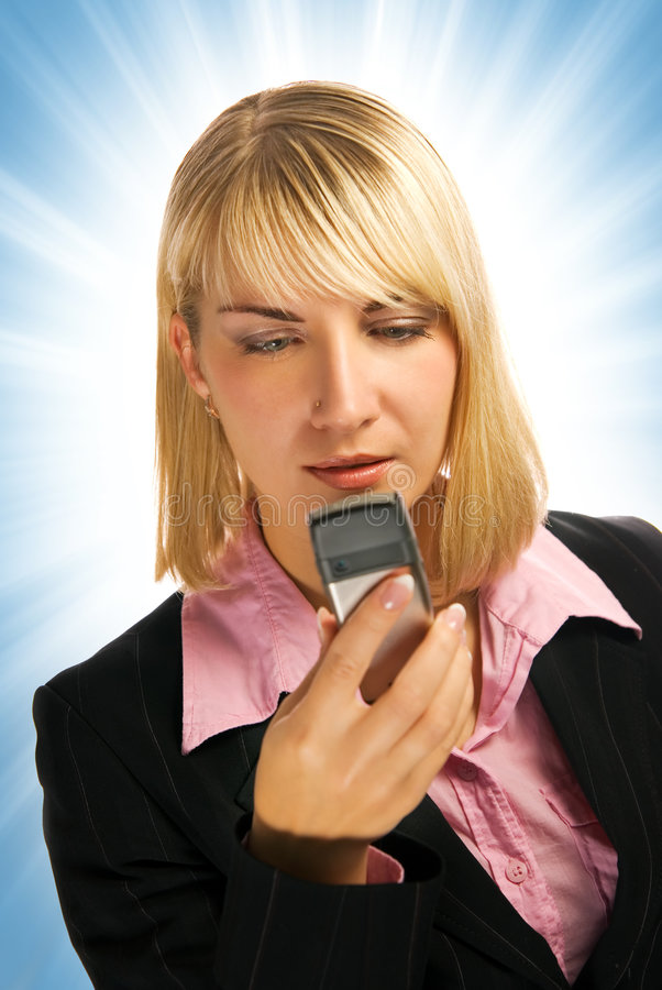 Beautiful business woman. Typing sms on her mobile phone royalty free stock photo