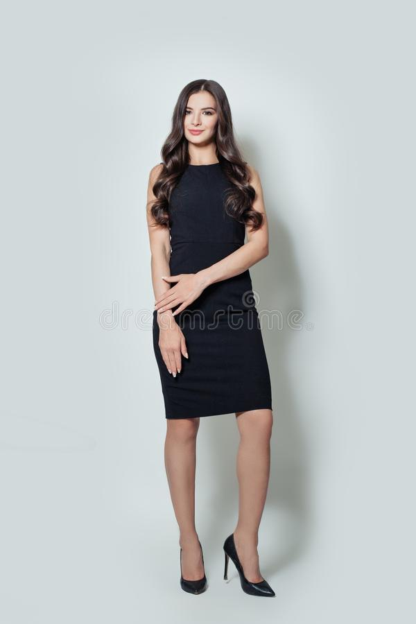 Beautiful business woman in black dress standing against white wall background royalty free stock image