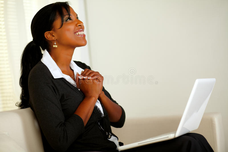 Beautiful business woman on black suit and smiling. Portrait of a beautiful business woman on black suit smiling and looking up and thanking while sitting on stock photos