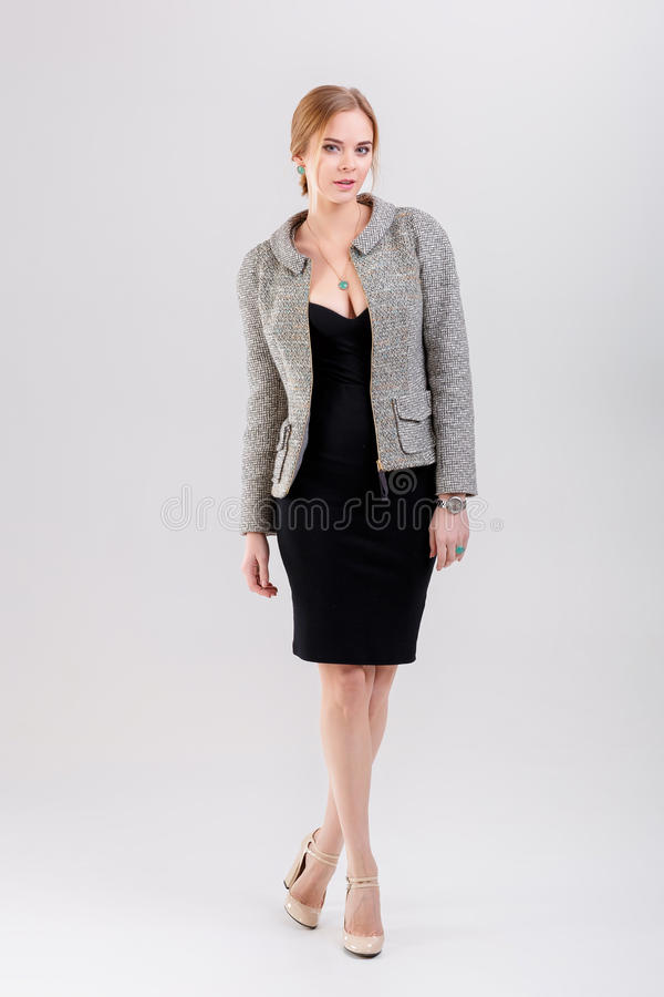 beautiful business woman blonde in black dress, jacket on gray royalty free stock photo