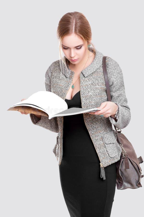 Beautiful business woman blonde in black dress, jacket reading a magazine on gray background. Young beautiful business woman blonde in black dress, jacket stock image