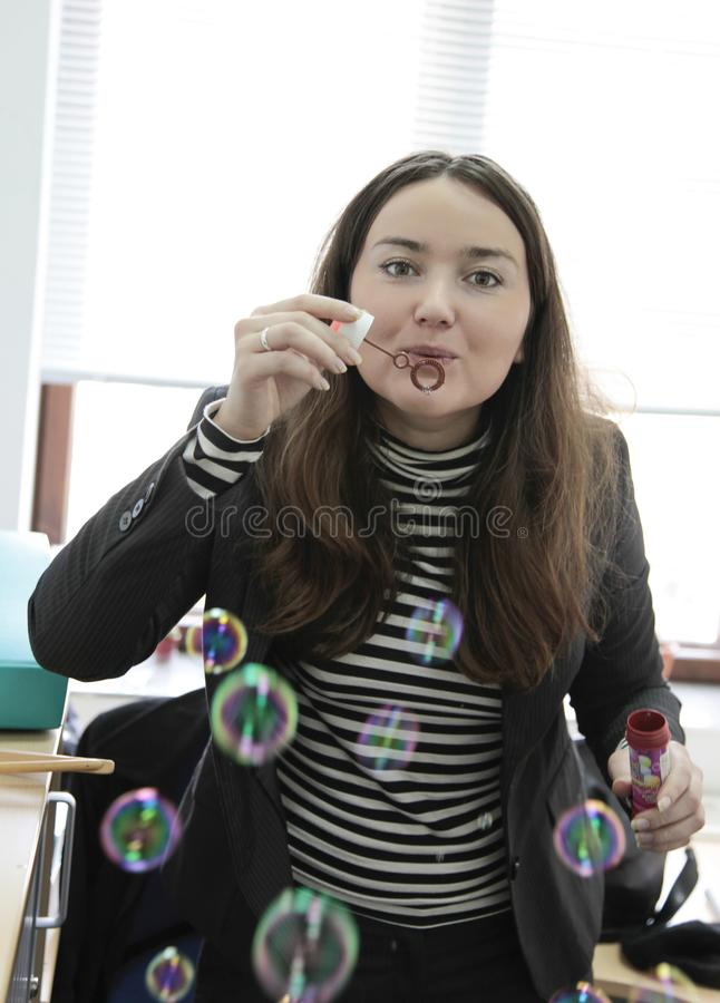 A beautiful business woman blowing soap bubbles in the office royalty free stock photos