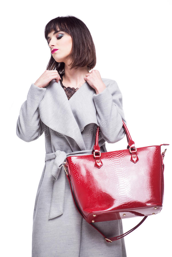 Beautiful business woman dressed in a gray coat holding a red bag royalty free stock photo