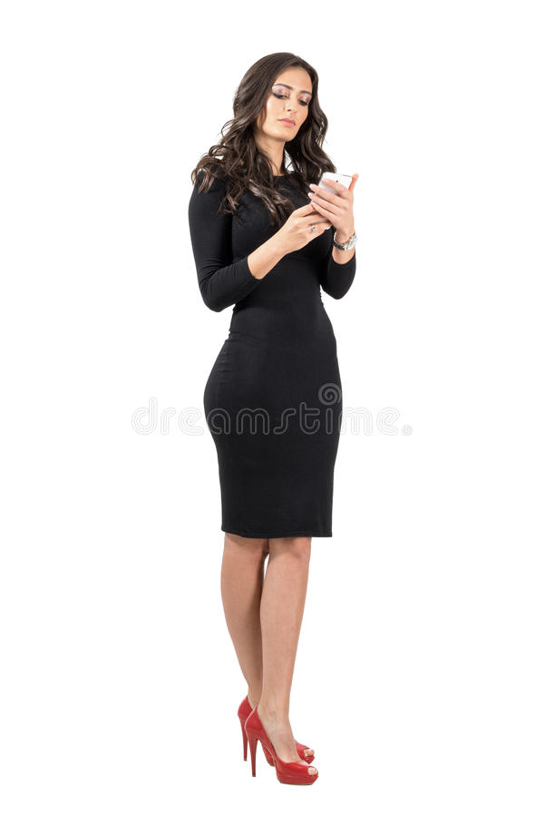Beautiful business woman in elegant black dress typing on her smartphone royalty free stock photo