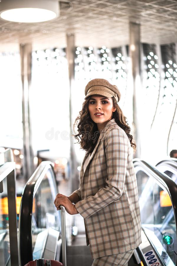 Beautiful business woman on escalator in airport. Job and travel concept royalty free stock image