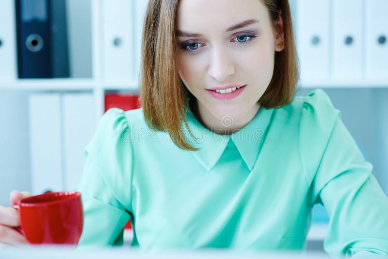 Young beautiful business woman holding cup of coffe and working at laptop. royalty free stock photography