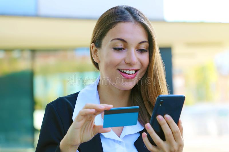 Beautiful business woman holds smart phone and credit card making shopping online outdoor office on break time. People and online royalty free stock photos
