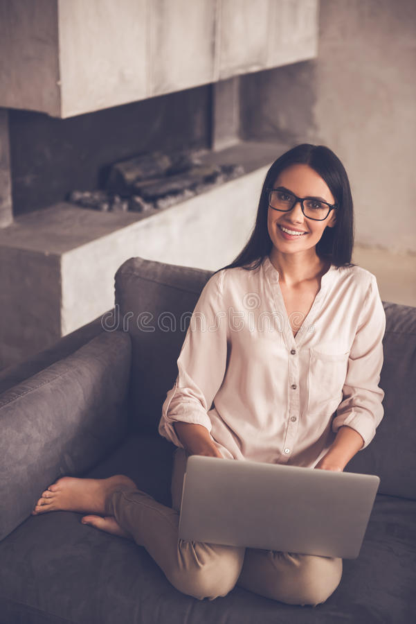 Beautiful business woman at home. Beautiful business woman in eyeglasses is using a laptop, looking at camera and smiling while sitting on couch at home stock photography