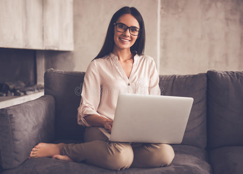Beautiful business woman at home. Beautiful business woman in eyeglasses is using a laptop, looking at camera and smiling while sitting on couch at home royalty free stock photo