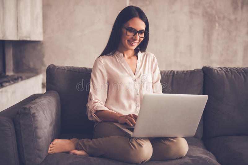 Beautiful business woman at home. Beautiful business woman in eyeglasses is using a laptop and smiling while sitting on couch at home stock image