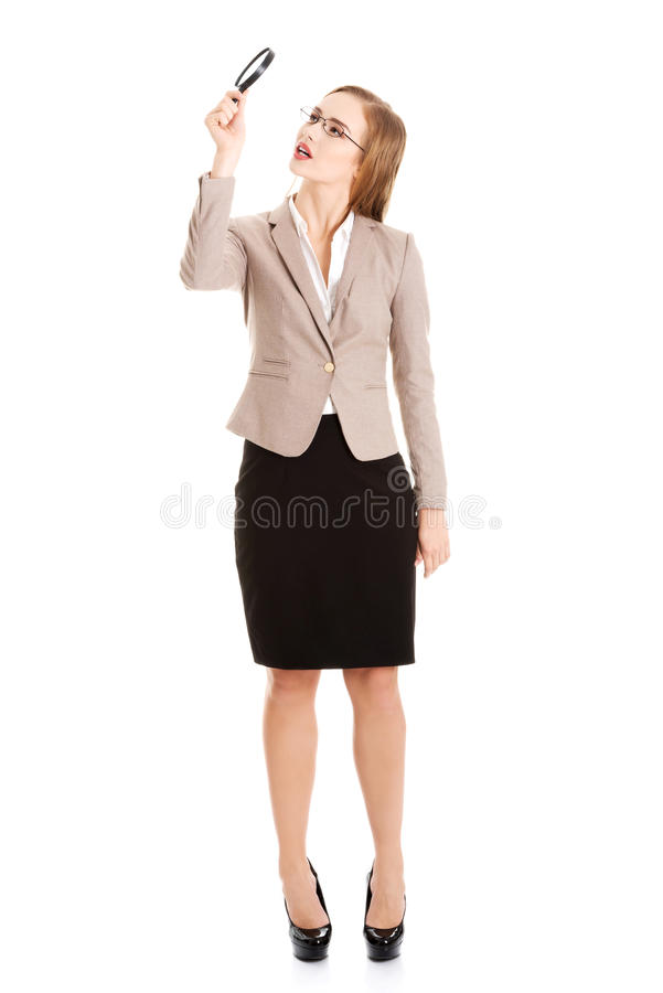 Beautiful business woman looking through magnifying glass. Isolated on white stock photography