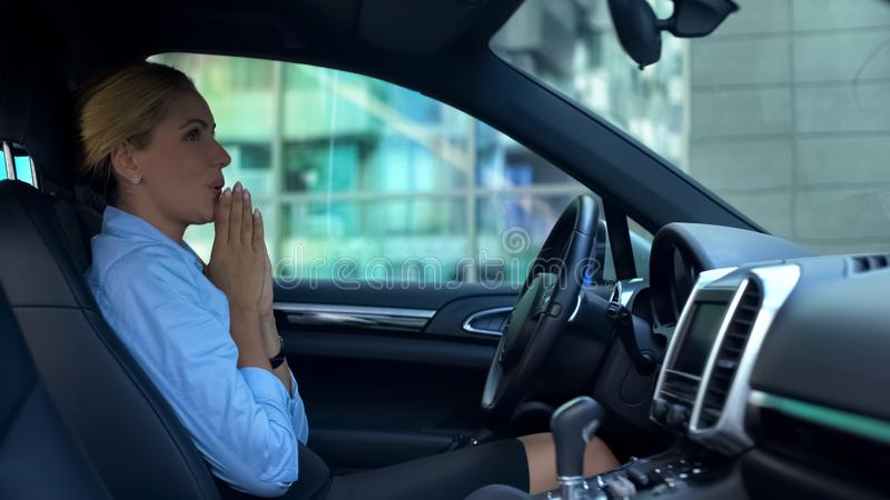 Beautiful business woman making wish sitting in her new car, success and wealth stock photography