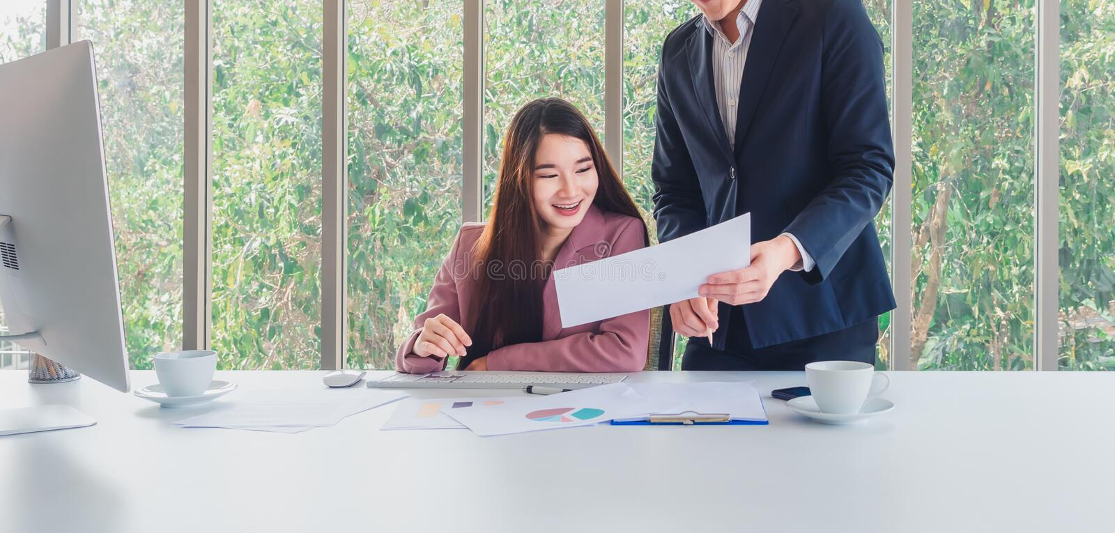 Beautiful business woman receive special offers of interest. Asian long hair beautiful business women in pink suit receive special offers of interest from a men stock image
