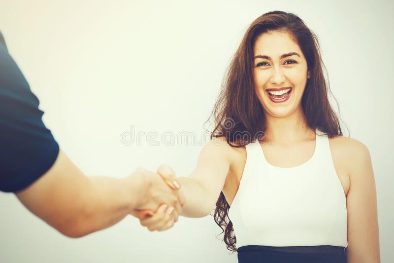 Beautiful business woman in smart casual dress shaking hands with male colleague stock photo