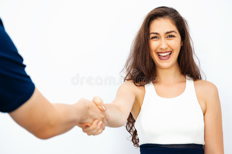 Beautiful business woman in smart casual dress shaking hands with male colleague stock images