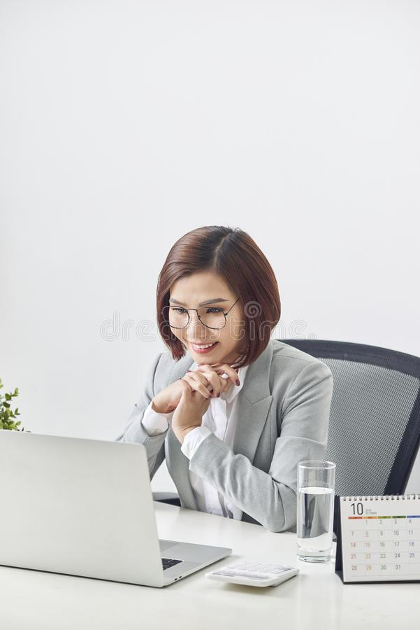 Beautiful business woman smile sitting at the desk working using laptop looking at screen typing on laptop over white background stock image