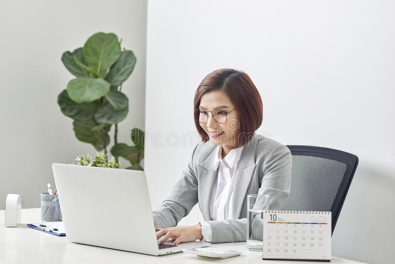 Beautiful business woman smile sitting at the desk working using laptop looking at screen typing on laptop over white background royalty free stock photography
