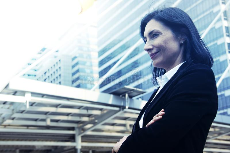 Beautiful business woman smiling and looking offices building background. Beautiful business woman smiling and looking offices building background, blue color stock photo