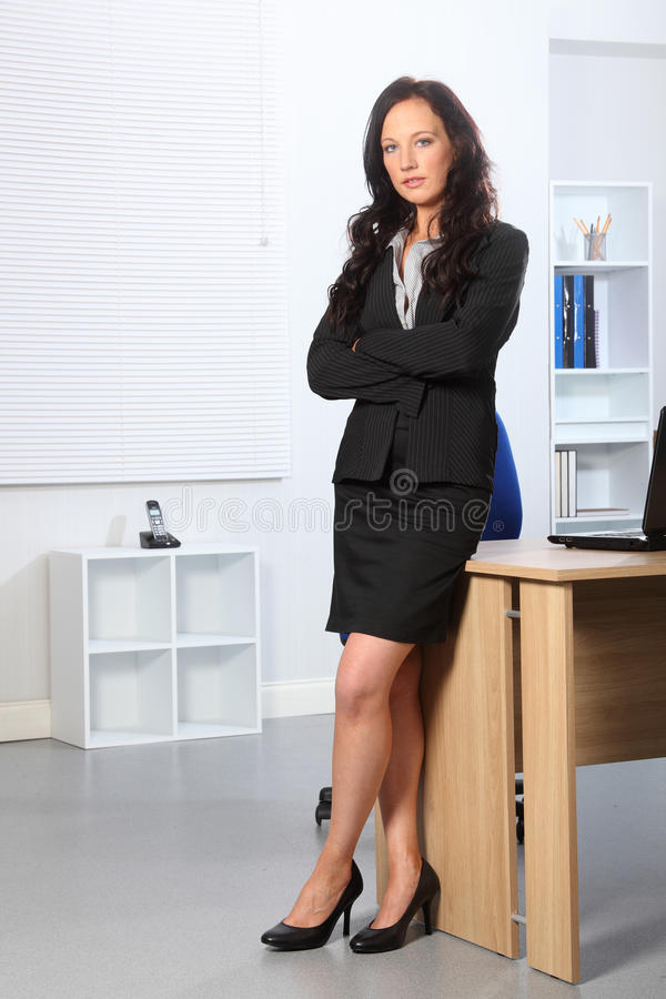 Beautiful business woman standing arms folded. Beautiful young business woman standing in office with her arms folded. She has a serious expression on her face stock photo