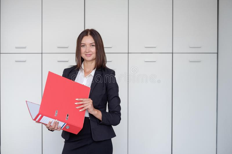 Beautiful business woman stands with a red folder in hands in a office royalty free stock photos