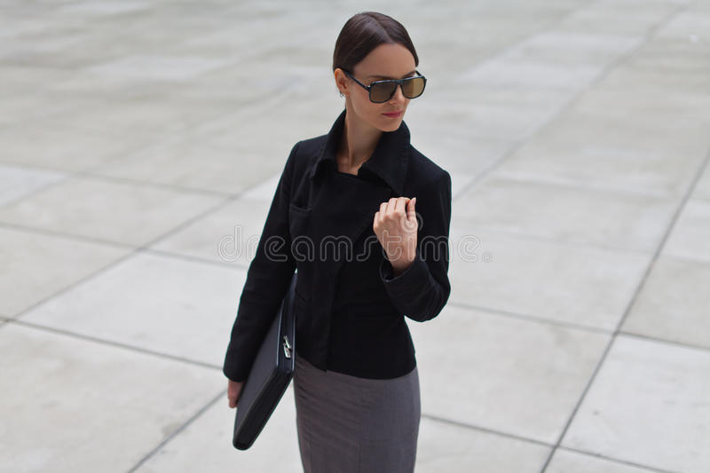 Beautiful business woman is wearing sunglasses royalty free stock photography