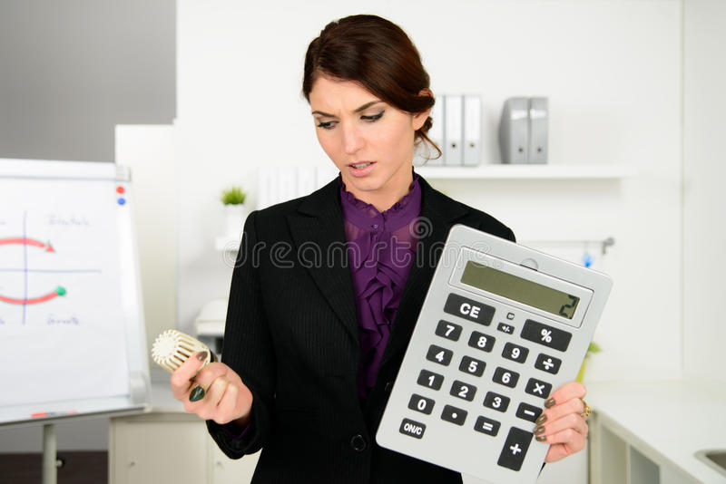 Beautiful business woman worry about heating costs. In office royalty free stock photography