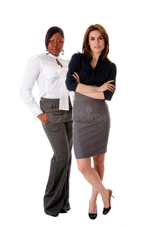 Beautiful business women. Beautiful Caucasian and African American business women standing next to each other as the dreamteam, isolated royalty free stock images