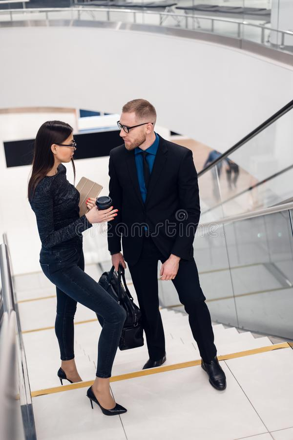 Beautiful business woman and man their holding a tablet in hands and talking to each other while standing at staircase stock images