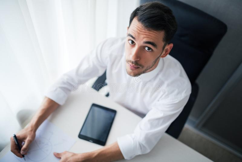Beautiful businessman working on a device, gadget in the office, sitting on the chair looking at the camera and writing royalty free stock photography