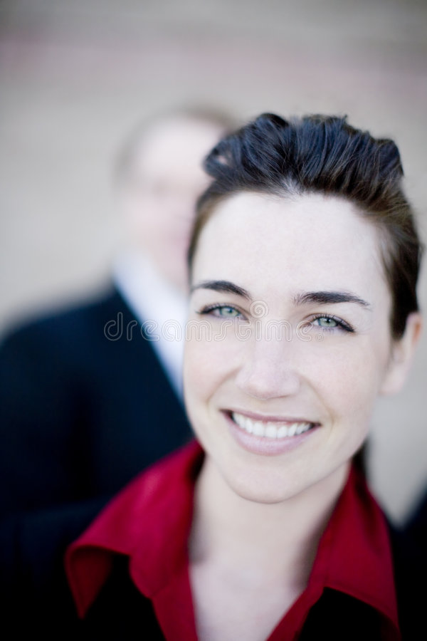 Beautiful businesswoman. Close view of beautiful young businesswoman wearing red collar shirt with businessman in background royalty free stock image