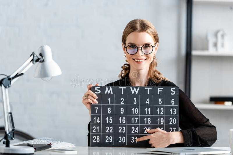 Beautiful businesswoman in black clothes and glasses holding calendar and smiling. At camera stock images