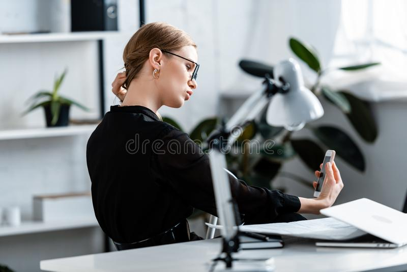 Beautiful businesswoman in black clothes and glasses looking. At smartphone royalty free stock photos
