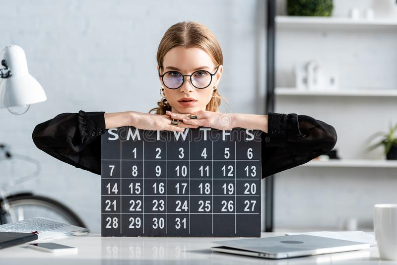 Beautiful businesswoman in black clothes and glasses sitting on chair and. Holding a calendar stock image