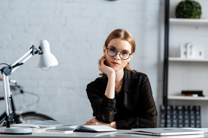 Beautiful businesswoman in black clothes and glasses sitting on chair and. Holding chin royalty free stock photography