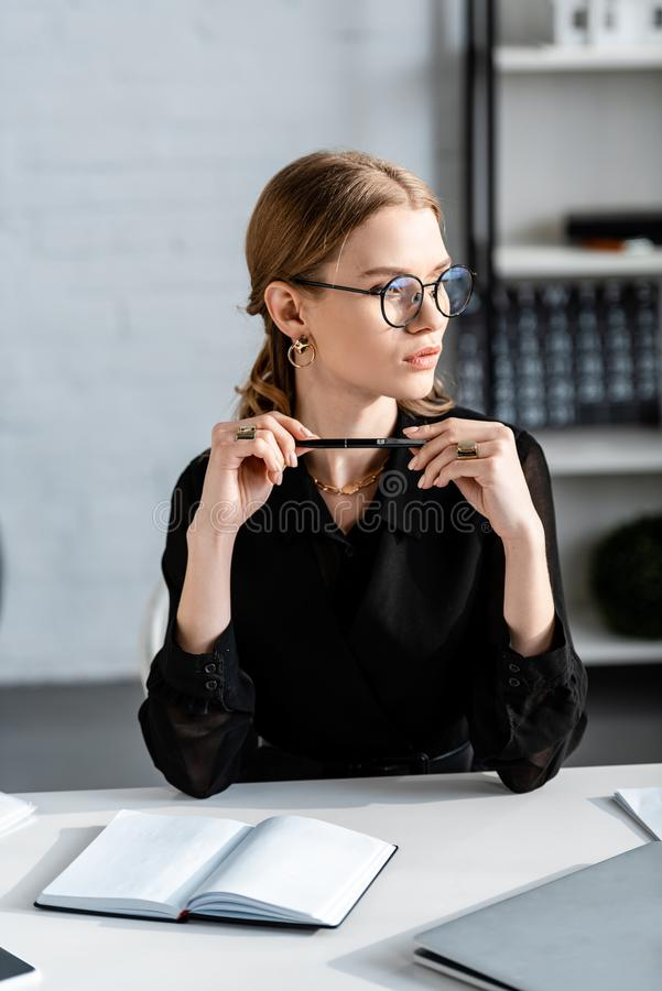 Beautiful businesswoman in black clothes and glasses sitting on chair and. Holding pen royalty free stock image