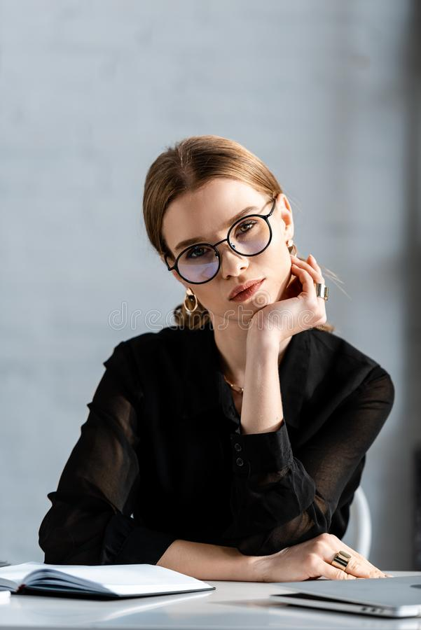 Beautiful businesswoman in black clothes and glasses sitting on chair and looking. At camera royalty free stock image