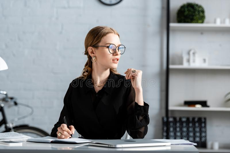 Beautiful businesswoman in black clothes and glasses sitting on chair and whiting. In note stock images