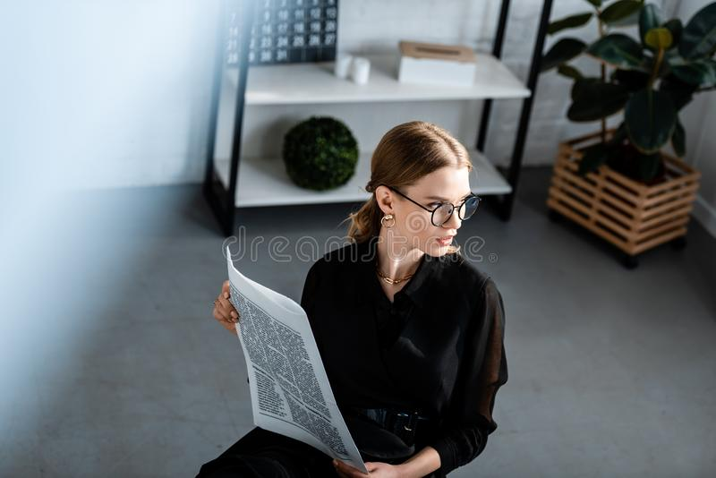 Beautiful businesswoman in black clothes and glasses sitting at table and. Holding newspaper royalty free stock photos