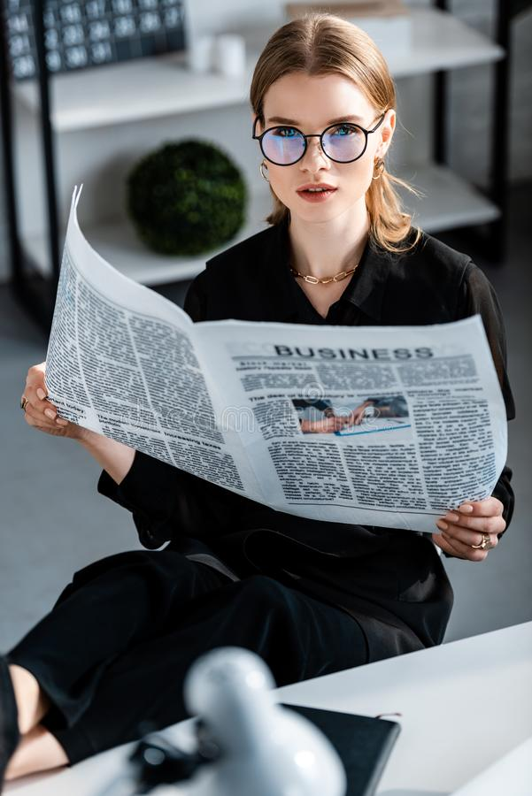 Beautiful businesswoman in black clothes and glasses sitting at table and holding newspaper while looking. At camera royalty free stock photography