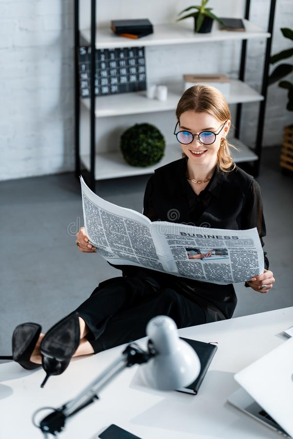 Beautiful businesswoman in black clothes and glasses sitting at table and. Reading newspaper royalty free stock photos