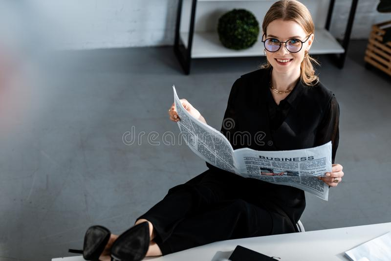 Beautiful businesswoman in black clothes and glasses sitting at table and smiling. At camera royalty free stock image