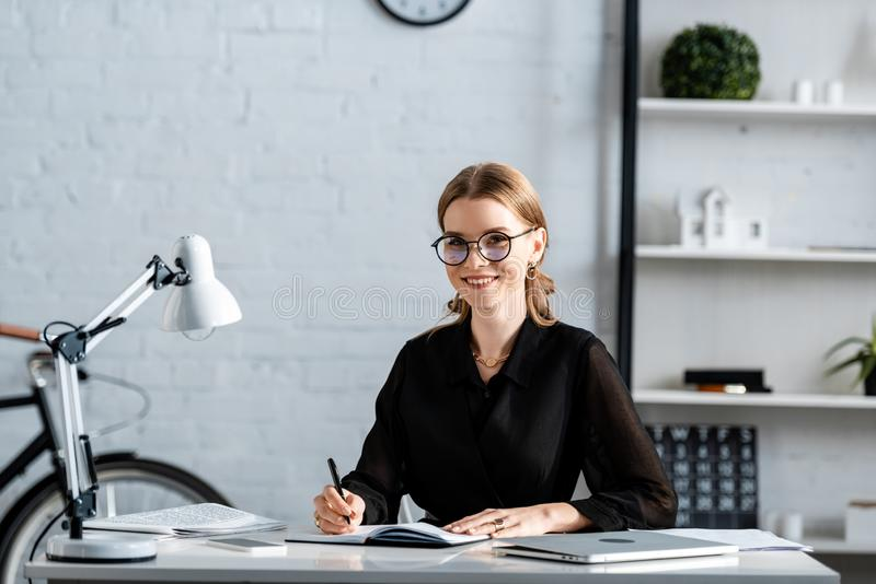 Beautiful businesswoman in black clothes and glasses smiling and writing. In note royalty free stock images
