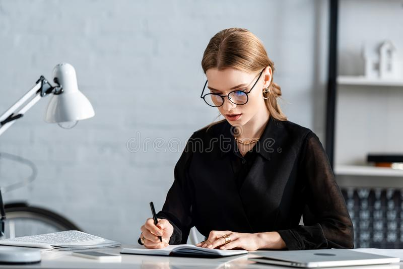 Beautiful businesswoman in black clothes and glasses  writing and sitting. On chair stock images