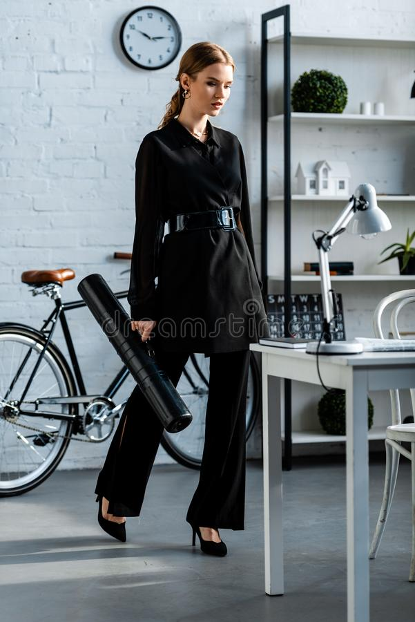 Beautiful businesswoman in black clothes looking at table and holding paper tube. At office stock images