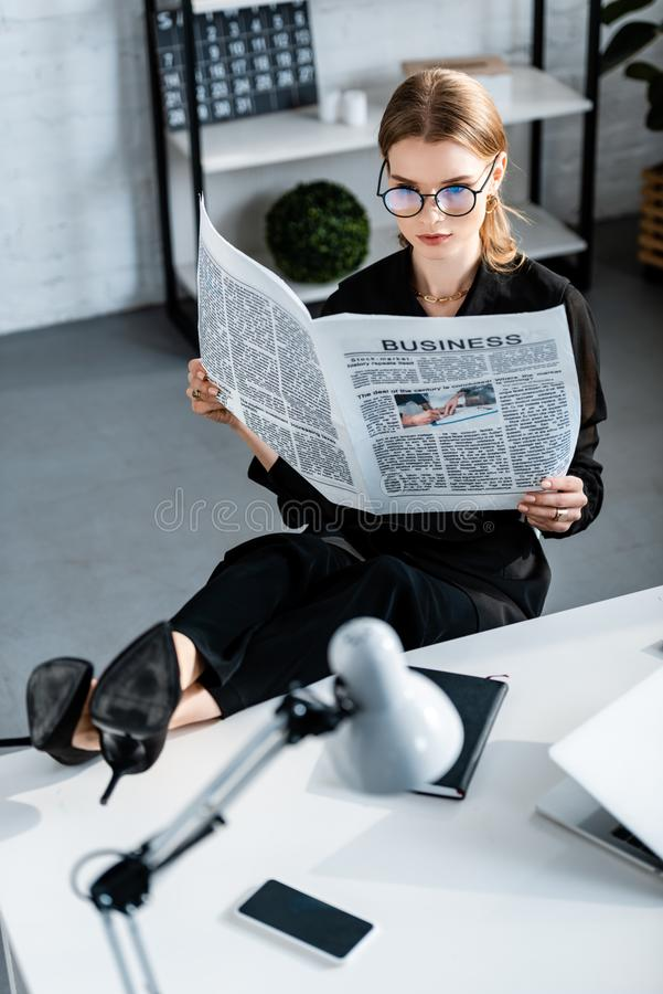 Beautiful businesswoman in black clothes and shoes sitting at table and. Holding newspaper stock photography