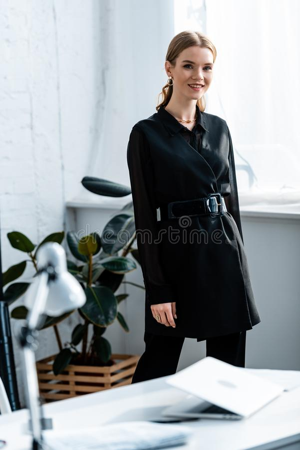 Beautiful businesswoman in black clothes smiling at camera. At office royalty free stock images