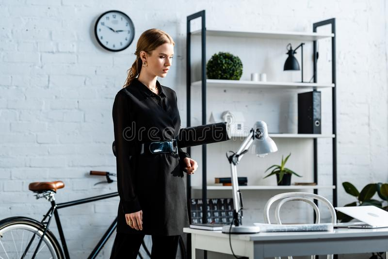 Beautiful businesswoman in black clothes standing at office and. Holding paper tube royalty free stock images